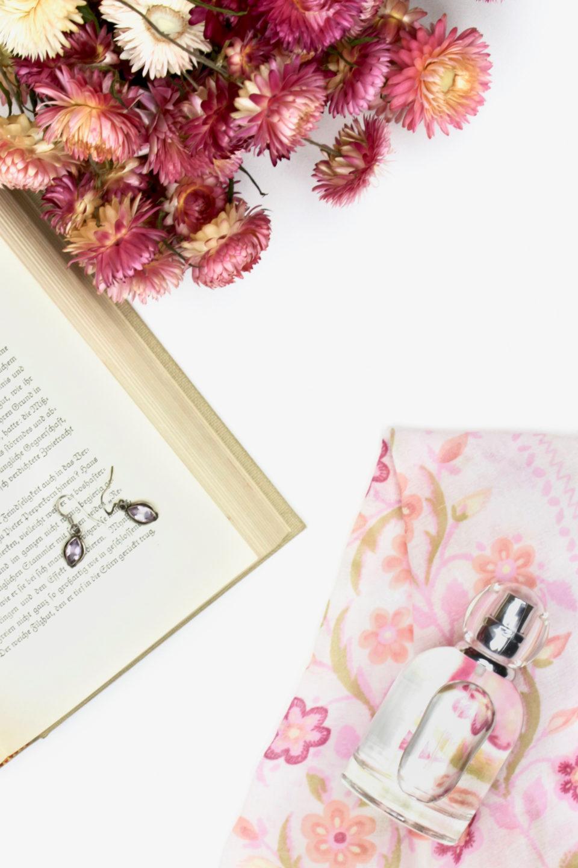 beauty flatlay flowers book earrings perfume scarf